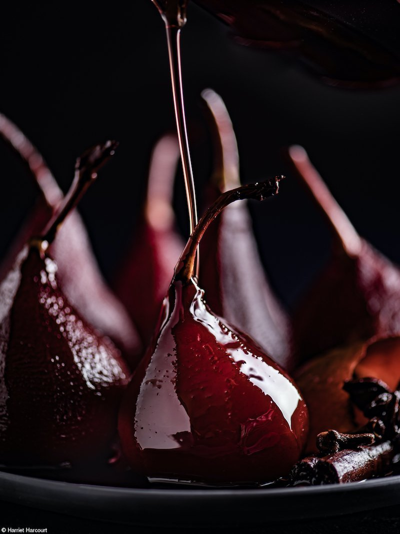 Pouring the spiced wine syrup over the poached pears before serving